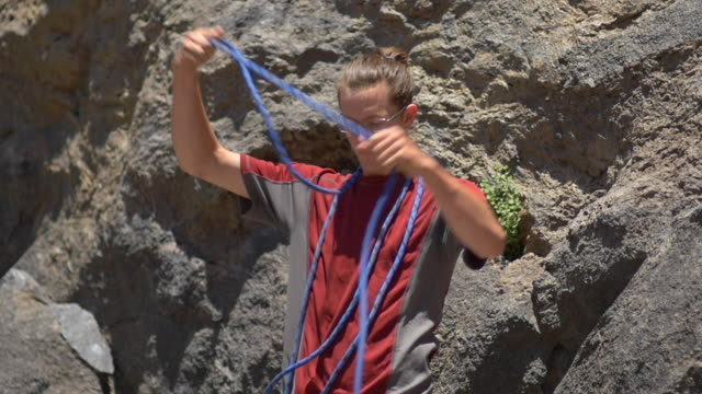 stockvideo's en b-roll-footage met a young man preparing his rope before going rock climbing. - slow motion - uitfaden