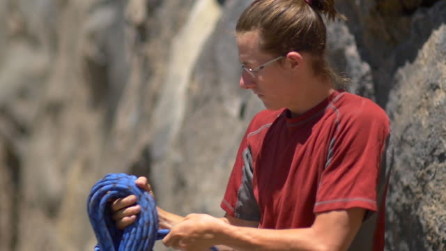 a young man preparing his rope before going rock climbing. - slow motion - climbing rope stock videos & royalty-free footage