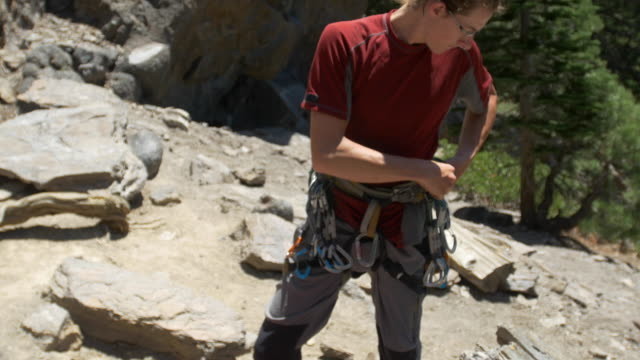 a young man preparing his rope before going rock climbing. - climbing rope stock videos & royalty-free footage