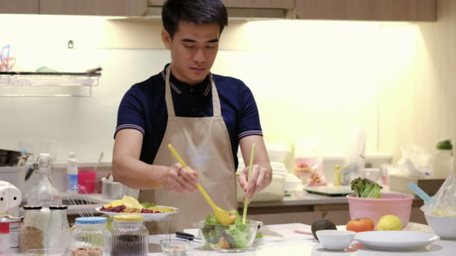 Young man preparing salad