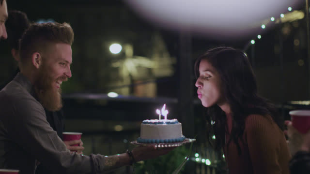 vídeos de stock, filmes e b-roll de ms slo mo. young man presents girlfriend with birthday cake and friends cheer as she blows out candles at chicago rooftop party. - aniversário