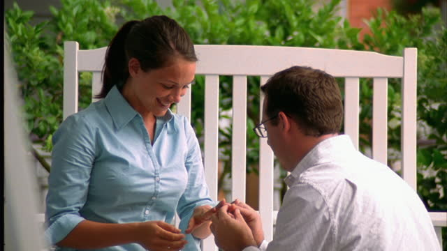 A young man proposes to his girlfriend on her front porch.