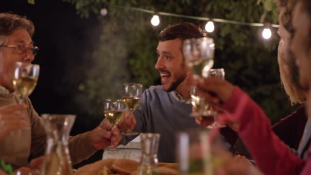 若い男が夜のピクニック用のテーブルで乾杯 - 談笑する点の映像素材/bロール