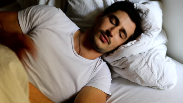 young man pulling blanket on bed at home - sdraiato video stock e b–roll