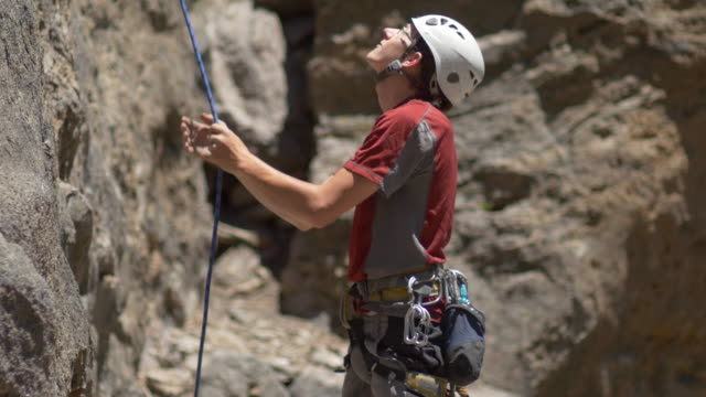 a young man pulling his rope down after rock climbing. - climbing rope stock videos & royalty-free footage