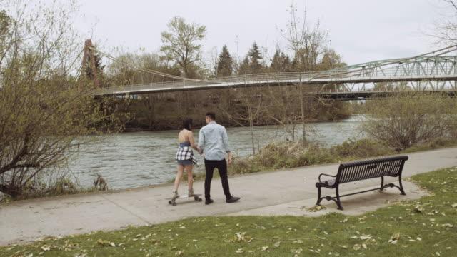 Jonge man trekken zijn significante andere op een longboard