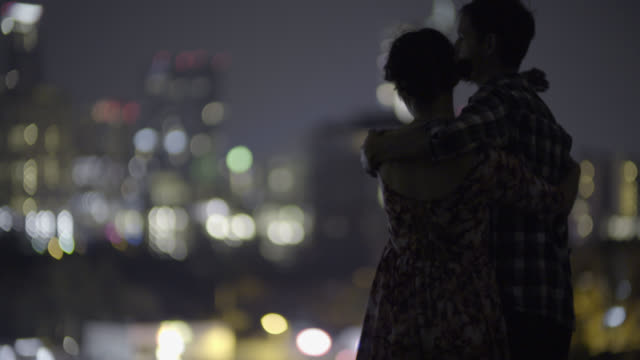 Young man pulls girlfriend close to him as they look out over the Austin, Texas skyline at night