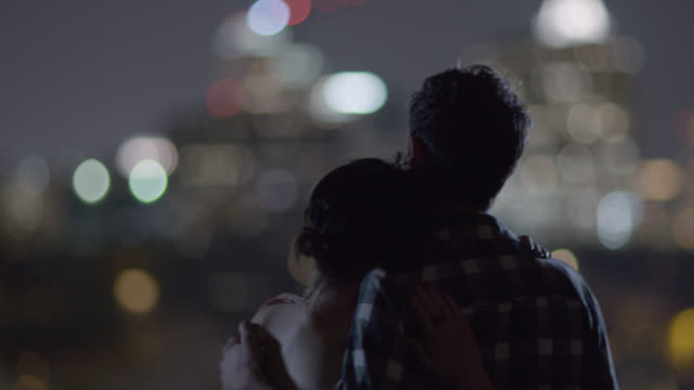 Young man pulls girlfriend close to him as they look out together on a city skyline at night
