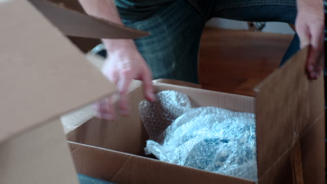 stockvideo's en b-roll-footage met young man pulls vase out of a box - kartonnen doos