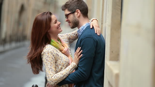 young man pulls woman into an embrace on paris street corner. - vicolo video stock e b–roll