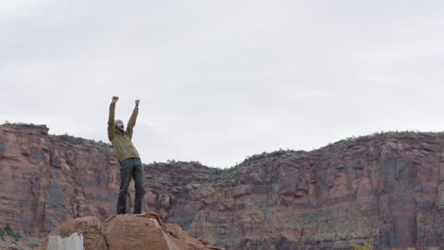 Young man pumps fists in the air and cheers after climbing rocky peak in Moab, Utah.