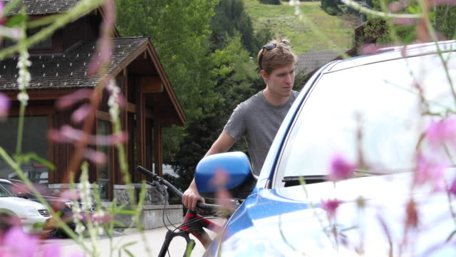 young man pushes bike away from car, in lot - anticipation stock videos & royalty-free footage