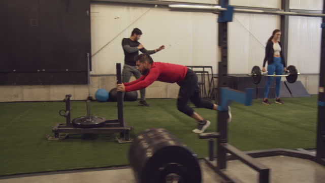 ts, young man pushing a sled with weights in a gym - effort stock videos & royalty-free footage