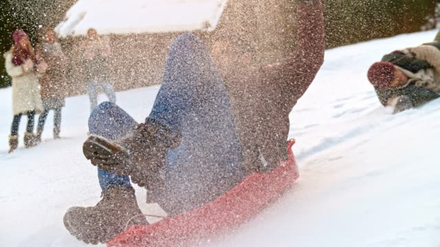 SLO MO Young man pushing his male friend on the sledge down the hill and falling to the ground laughing