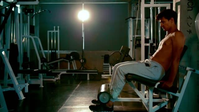 Junger Mann schob Gewichten von Bein im Fitness-Studio