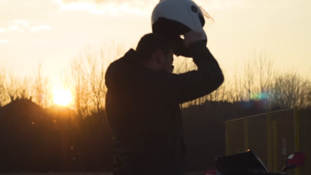 a young man puts a helmet to go on a journey - crash helmet stock videos & royalty-free footage