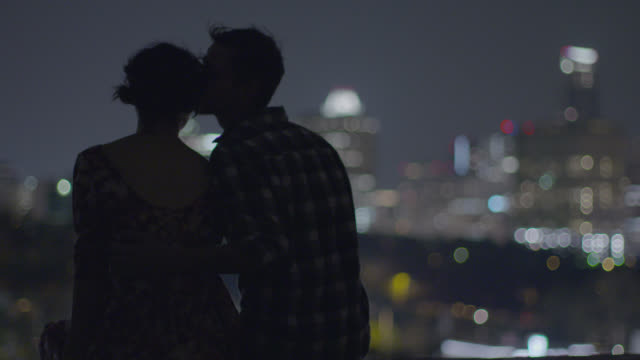 Young man puts his arm around girlfriend and kisses her forehead as they look out over Austin skyline