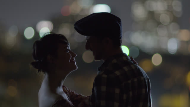 vídeos y material grabado en eventos de stock de young man puts his arm around girlfriend and kisses her forehead as they look out on a city skyline - propuesta