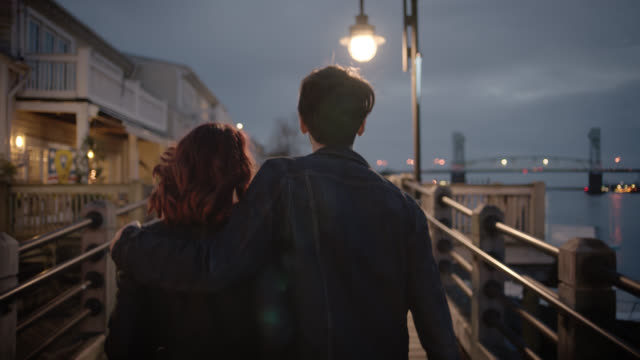 SLO MO. Young man puts his arm around girlfriend as they stroll down romantic riverfront boardwalk at night.