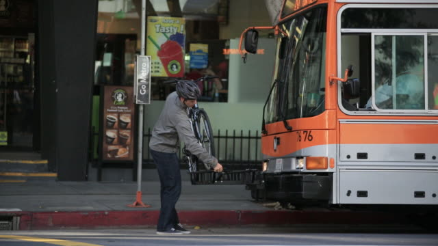 vidéos et rushes de young man putting bike on city bus - casque de vélo