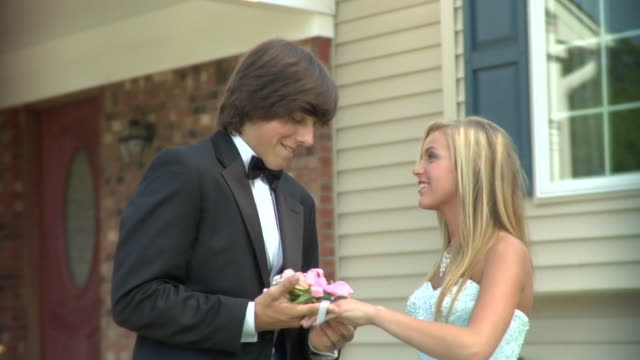 cu, young man putting corsage on girl's (16-17) wrist in front of house, edison, new jersey, usa - teenagerpaar stock-videos und b-roll-filmmaterial