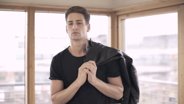 vidéos et rushes de a young man putting his leather jacket on. - veste et blouson