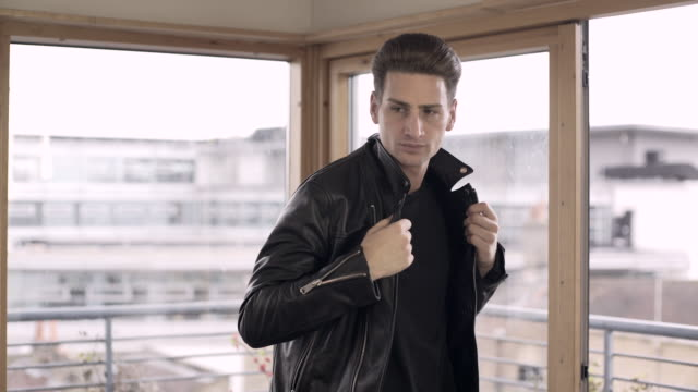 a young man putting his leather jacket on. - leather jacket stock videos and b-roll footage