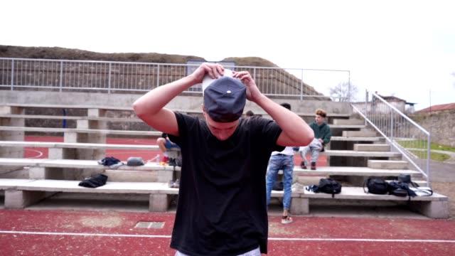 vidéos et rushes de jeune homme mettant sur sa casquette - casquette