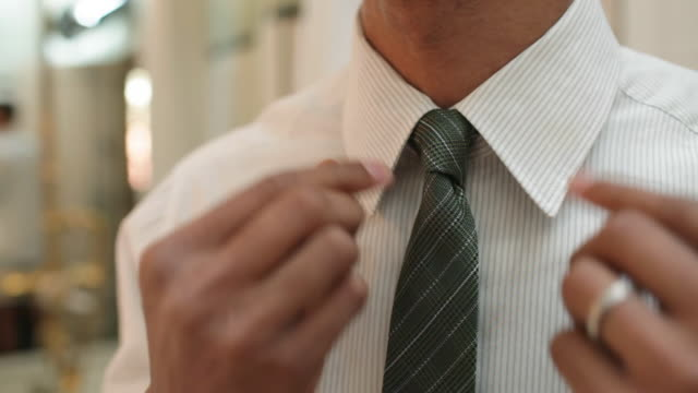 young man putting on tie - shirt and tie stock-videos und b-roll-filmmaterial