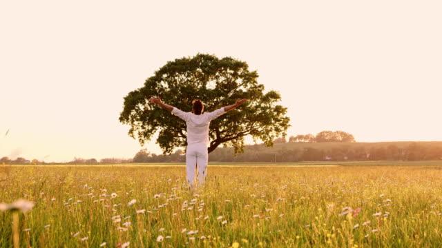 vídeos de stock, filmes e b-roll de ws jovem levantando os braços para o céu de uma posição de agachamento - braço humano