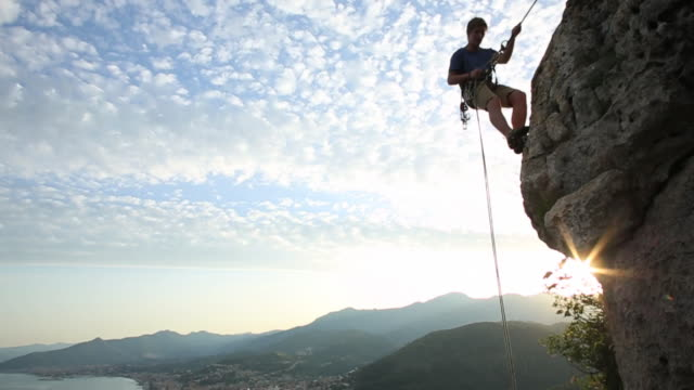young man rappels (abseils) as sun rises behind - abseiling stock videos & royalty-free footage