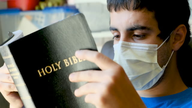 vídeos de stock e filmes b-roll de young man reading a bible wearing a surgical mask - bíblia