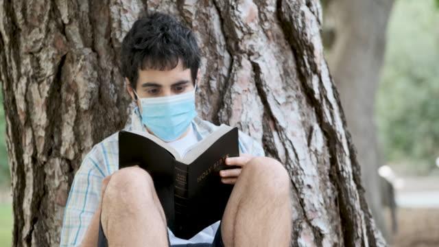 giovane che legge una bibbia indossando una maschera chirurgica - one man only video stock e b–roll