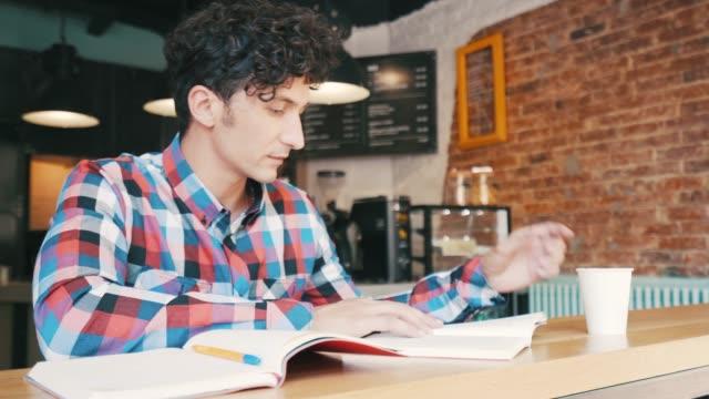 vídeos de stock, filmes e b-roll de jovem lendo um livro no café. - reading berkshire