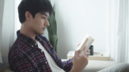 Young man reading a book in his apartment