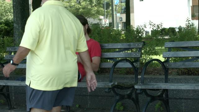 vídeos y material grabado en eventos de stock de a young man reading a book outside on a bench in new york city - sólo hombres jóvenes