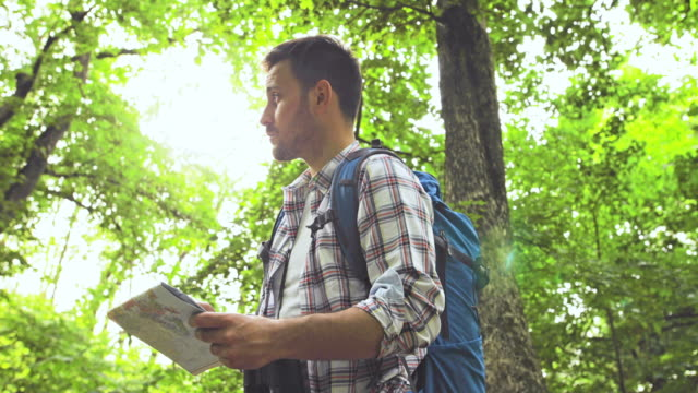 young man reading a map and looking through binoculars while orienteering in the forest. - looking through an object stock videos & royalty-free footage