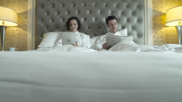 Young man reading a newspaper and a woman using a tablet in bed