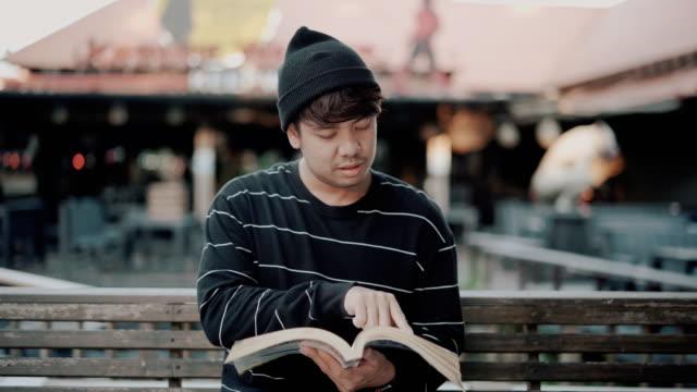 stockvideo's en b-roll-footage met jonge mens die boek in de tuin leest - huisbezoek