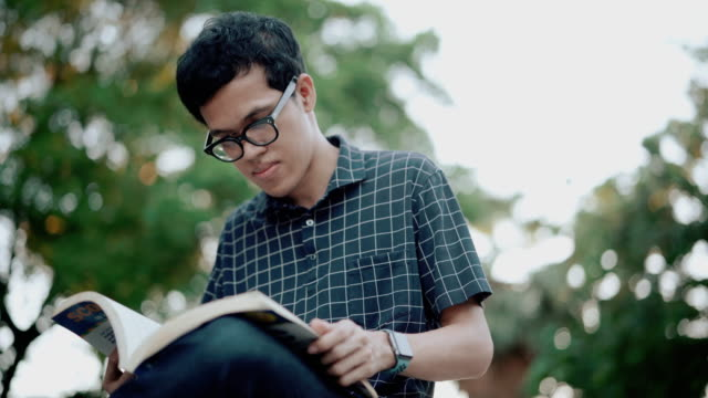 young man reading book in the garden - reading glasses stock videos & royalty-free footage