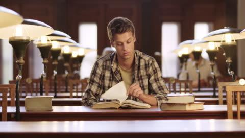 vidéos et rushes de ds jeune homme la lecture dans la bibliothèque - jeunes hommes
