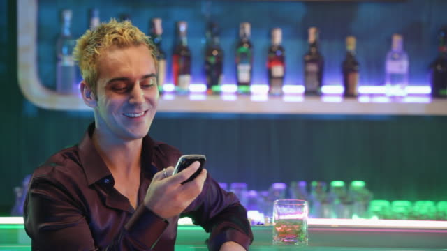 Young man reading text messaging at bar counter