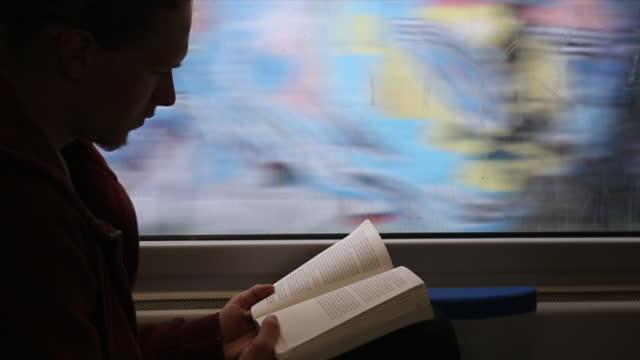 vidéos et rushes de livre de lectures du jeune homme lors d'un voyage sur le sentier - train
