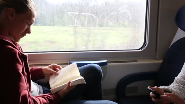 young man reads book while traveling on trail - public transport stock videos & royalty-free footage