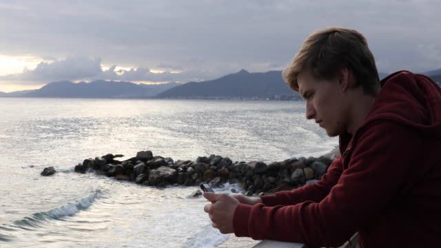 Young man relaxes beside car, looks off to sea while texting