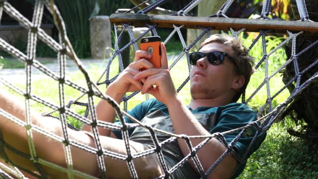 ung man slappnar i hängmattan medan textning på smart telefon - hängmatta sol bildbanksvideor och videomaterial från bakom kulisserna