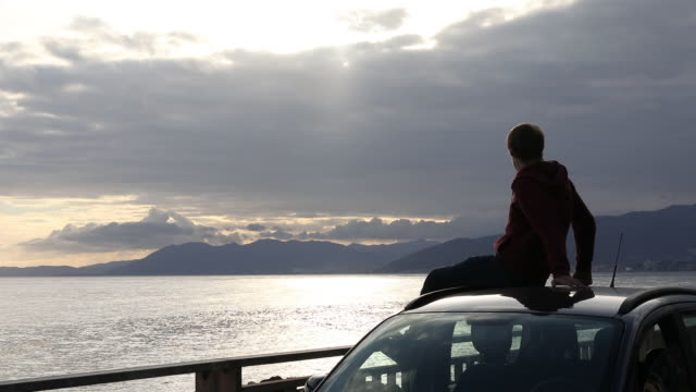 Young man relaxes on car roof, looks off to sea
