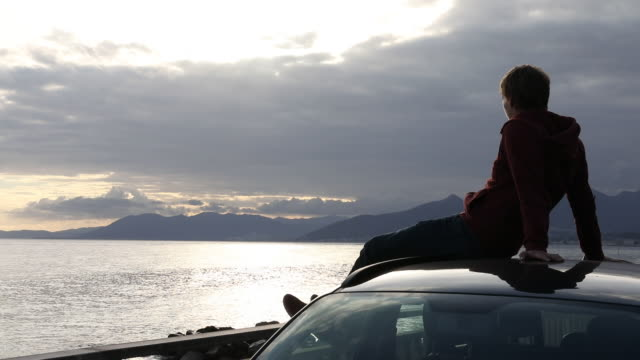 vídeos de stock e filmes b-roll de young man relaxes on car roof, looks off to sea - jeans