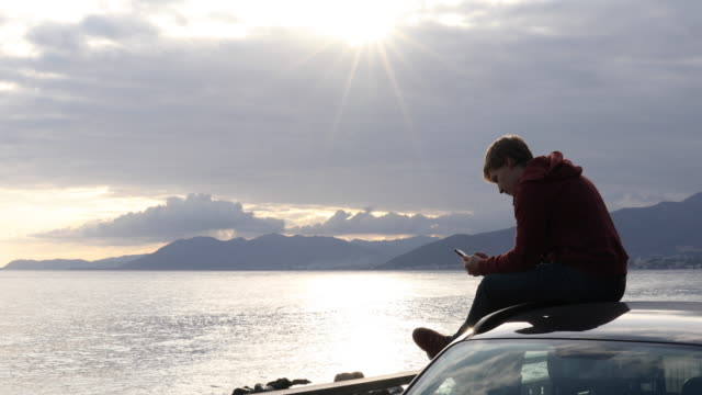 young man relaxes on car roof, texting on smart phone - jeans stock videos & royalty-free footage