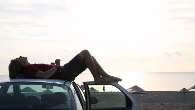 vidéos et rushes de young man relaxes on roof of car, above beach, sea - être étendu